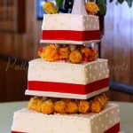 wedding-cake-red-ribbon-orange-flowers-white-cake