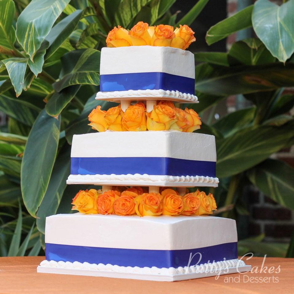 Photo of a blue ribbon orange flowers white wedding cake - Patty\'s ...